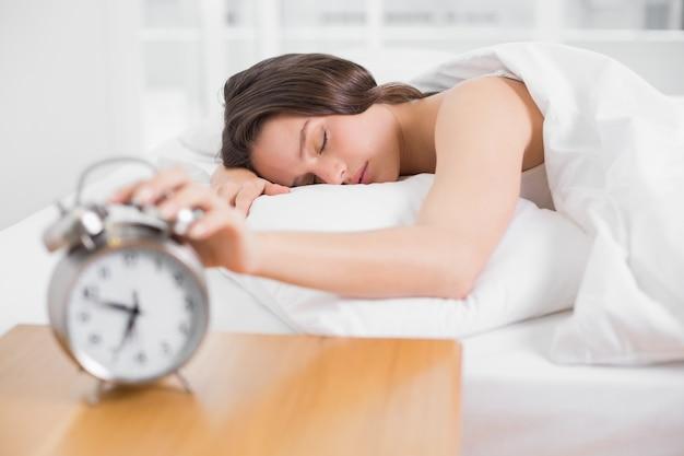 Femme au lit avec les yeux fermés, étendant la main au réveil