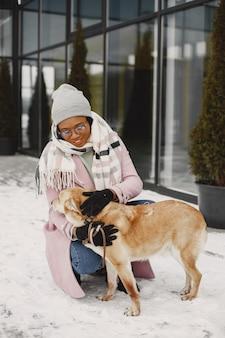 Femme au manteau rose, promener le chien