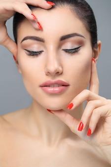 Femme au maquillage nude un vernis à ongles rouge