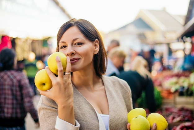 Femme au marché aux fruits avec des pommes dans les mains.