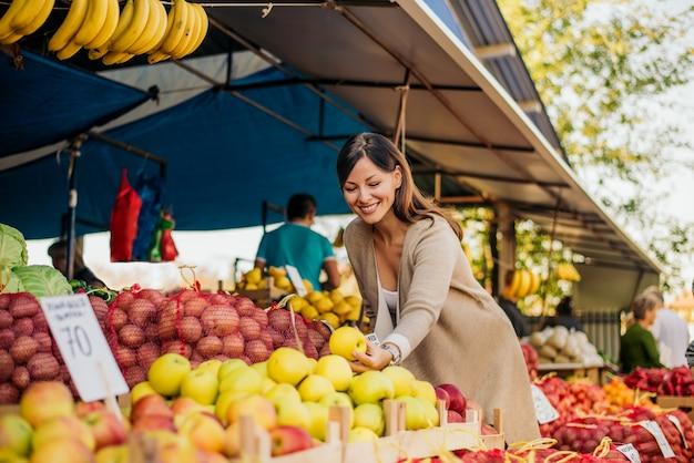 Femme au marché à la recherche de fruits et légumes.