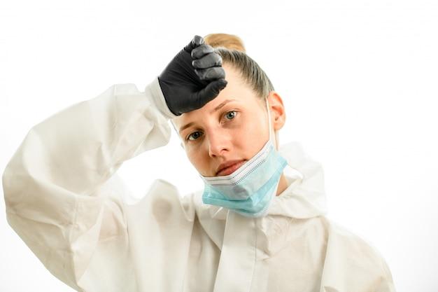 Femme au masque abattu s'essuie le front avec la main