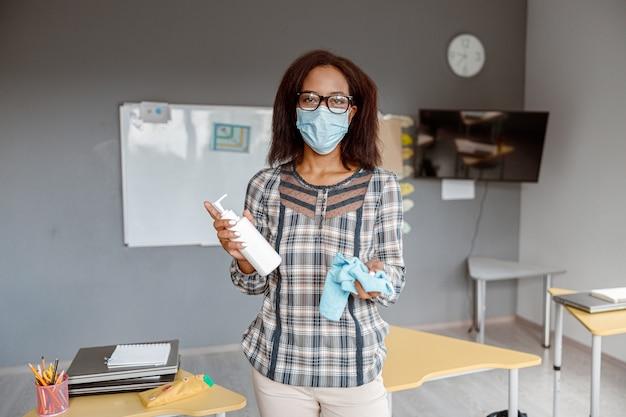Femme au masque facial nettoyant les tables avec un désinfectant antiseptique à l'école