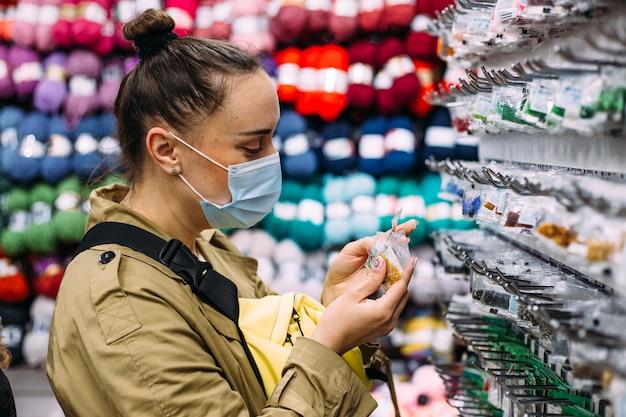 Femme au masque facial sélectionne des produits de perles dans le concept de magasinage d'artisanat