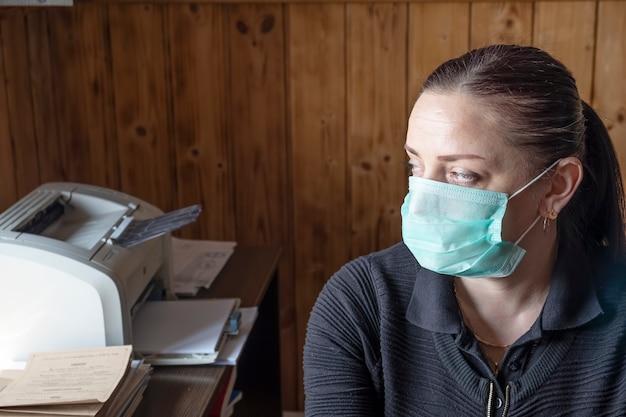Femme au masque médical au travail.