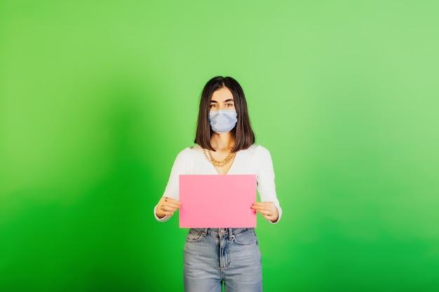 Femme au masque médical avec une feuille de papier vierge rose isolé sur fond vert.