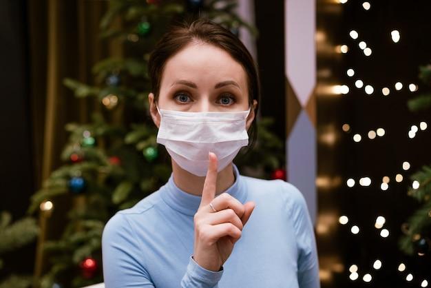 Femme au masque médical montre le geste du doigt pour être calme sur fond de bokeh