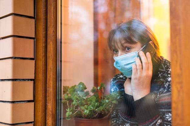 Femme au masque médical regardant à travers la fenêtre avec espoir