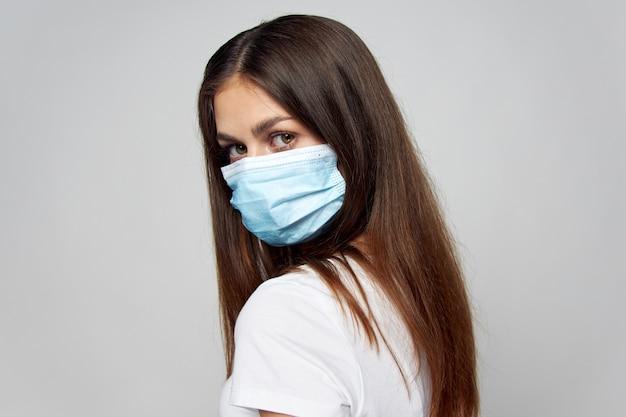 Femme au masque médical regarder devant les cheveux longs vue recadrée fond clair
