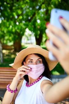 Femme au masque médical rose dans le parc prendre selfie par téléphone mobile, femme avec protection respiratoire est à l'extérieur tout en parlant et en discutant par vidéo par webcam sur smartphone