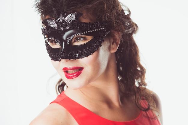 Femme au masque noir qui pose en studio