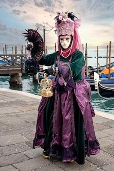 Femme au masque portant un costume de carnaval coloré sur la lagune de san marco. carnaval de venise, italie