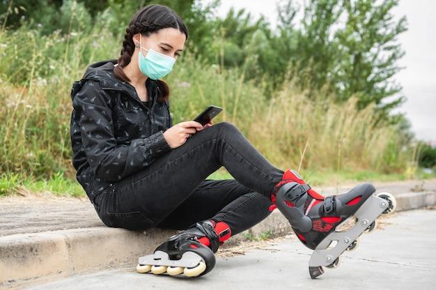 Femme au masque protecteur, en pause de patinage à roulettes, assis dans la rue et à l'aide de téléphone portable lors d'une épidémie de pandémie de coronavirus. fille urbaine à l'aide de téléphone, portant des patins à roulettes.