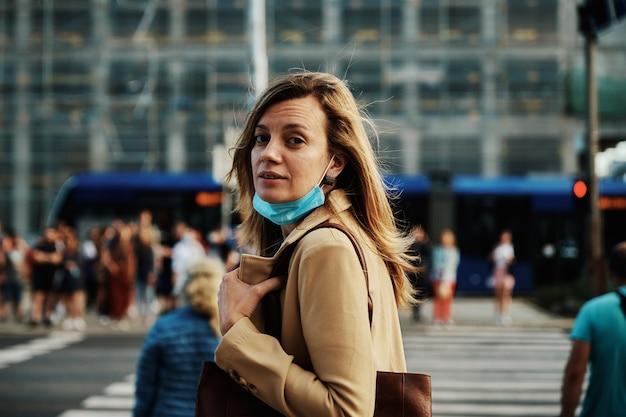 Une femme au masque de protection marche dans la rue de la ville