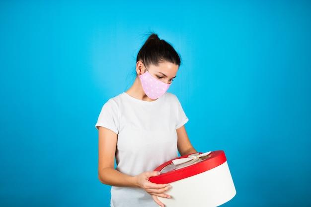 Femme au masque de protection rose tenir une grande boîte-cadeau en forme de coeur sur bleu