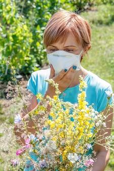 Femme au masque de protection tenant un bouquet de fleurs sauvages et essayant de lutter contre les allergies au pollen. lumière naturelle du jour. notion d'allergie.