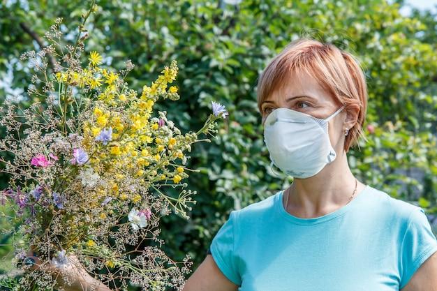 Femme au masque de protection tenant un bouquet de fleurs sauvages et essayant de lutter contre les allergies au pollen. notion d'allergie.