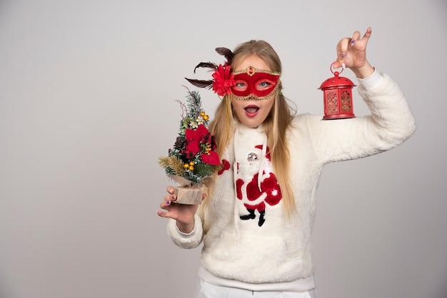 Femme au masque rouge montrant un cadeau de lampe et un pin étonnamment.