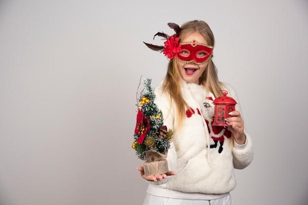 Femme au masque rouge montrant un cadeau de lampe et un pin.