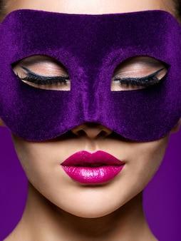 Femme au masque de théâtre violet sur le visage avec des lèvres violettes