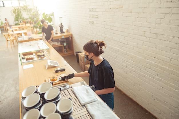 Femme au masque travaillant barista dans un café