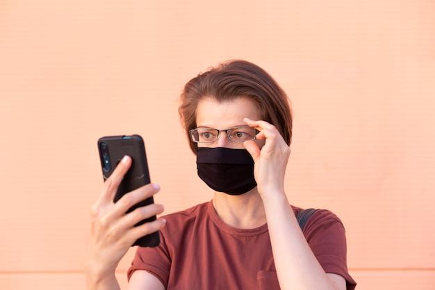 La femme au masque utilise un téléphone portable