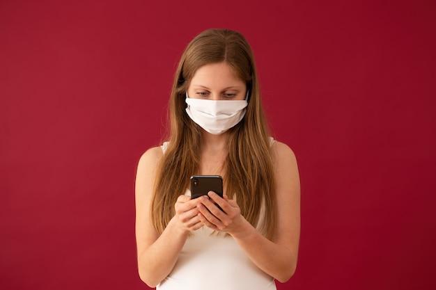 Femme au masque de visage textos sur téléphone mobile avec fond rouge
