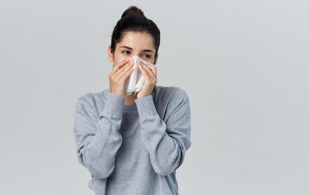 Femme au nez qui coule avec des problèmes de santé de serviette