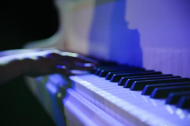 Femme au piano blanc sur la scène.