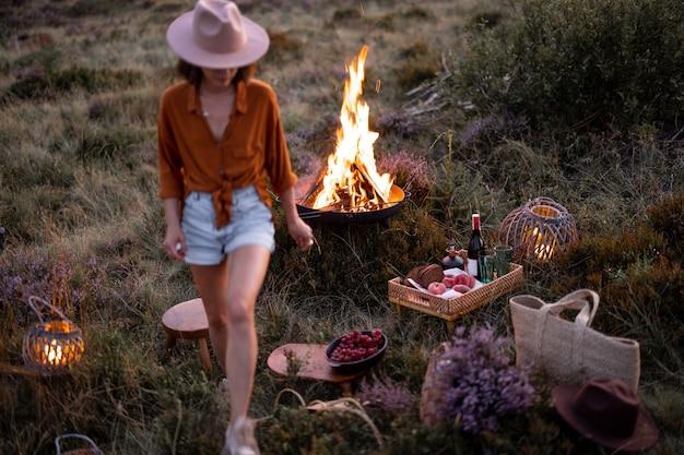 Femme au pique-nique avec feu de joie dans les montagnes