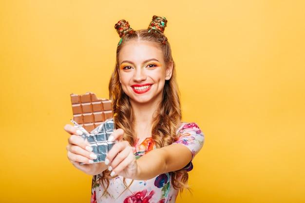 Femme au regard ludique mord un énorme chocolat