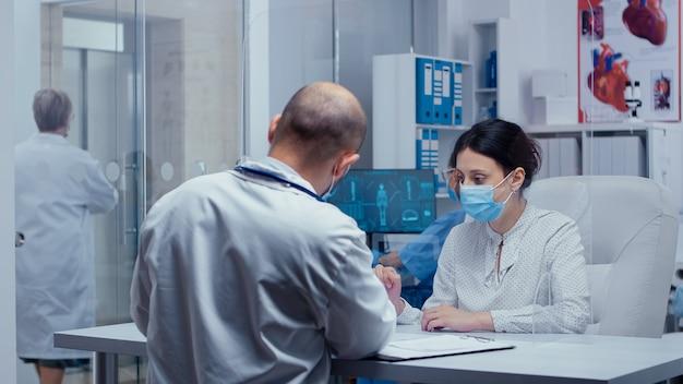 Femme au rendez-vous chez le médecin pendant covid-19 portant un masque et des gants, parlant avec un médecin à travers un mur de protection. consultation médicale dans le concept d'équipement de protection photo de la guérison mondiale du sras-cov-2