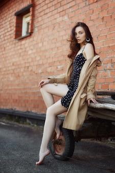 Femme au repos dans le village près des écuries, portrait d'une femme au soleil, style rustique. portrait d'une brune sexy dans un imperméable dans la nature. maquillage parfait, cosmétiques naturels