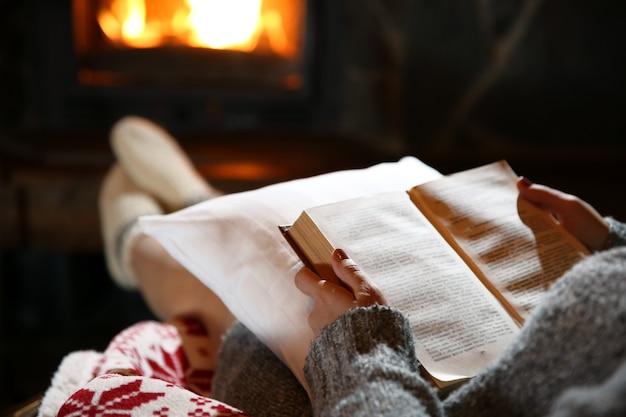 Femme au repos avec un livre près de la cheminée