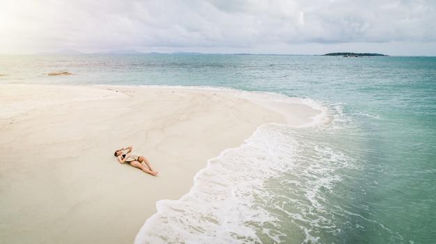 Une femme au soleil en bord de mer porte un bikini portant un chapeau de mer.