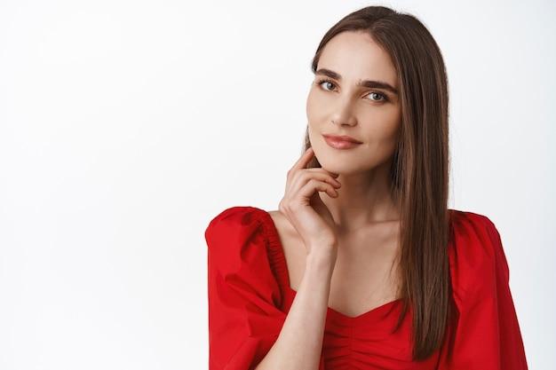 Femme au sourire sensuel, maquillage romantique et robe passionnée rouge, regardant, touchant la peau du visage, semblant réfléchie sur blanc.