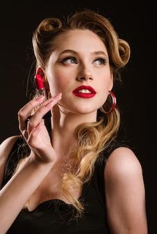 Femme au style rétro posant avec un rouge à lèvres rouge sur fond noir. portrait de pin-up