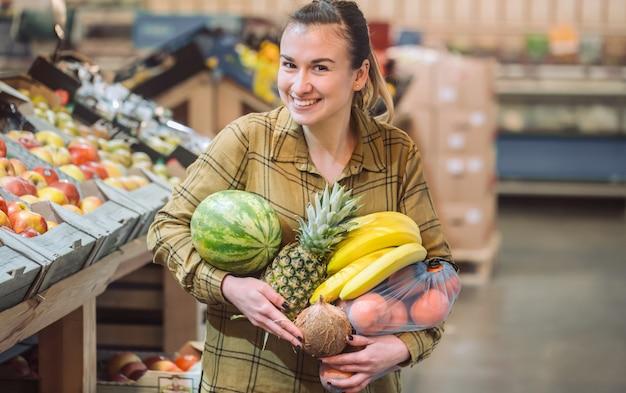 Femme au supermarché. belle jeune femme, faire du shopping dans un supermarché et acheter des légumes biologiques frais