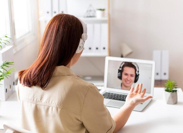 Femme au travail ayant un appel vidéo sur ordinateur portable