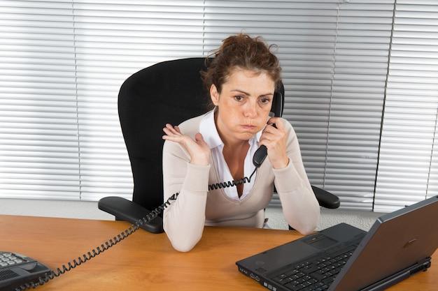 Femme au travail téléphonant au client