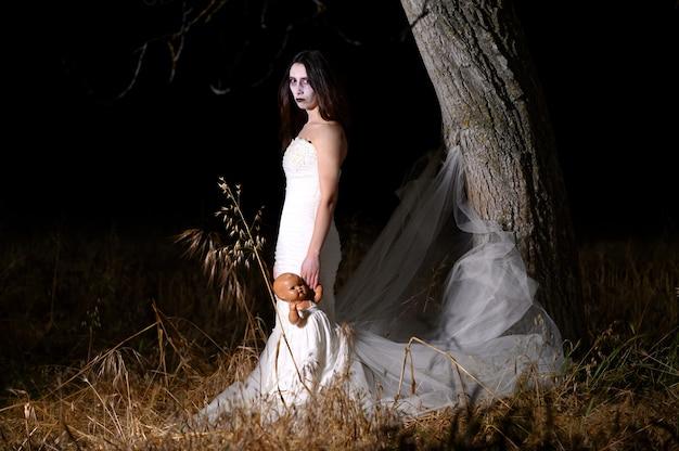 Femme au visage blanc et robe tenant une poupée