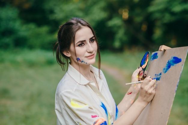 Femme au visage coloré peint dessin sur une toile