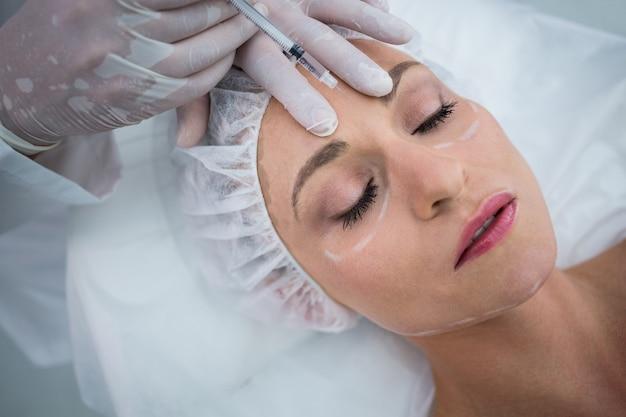 Femme au visage marqué recevant une injection de botox