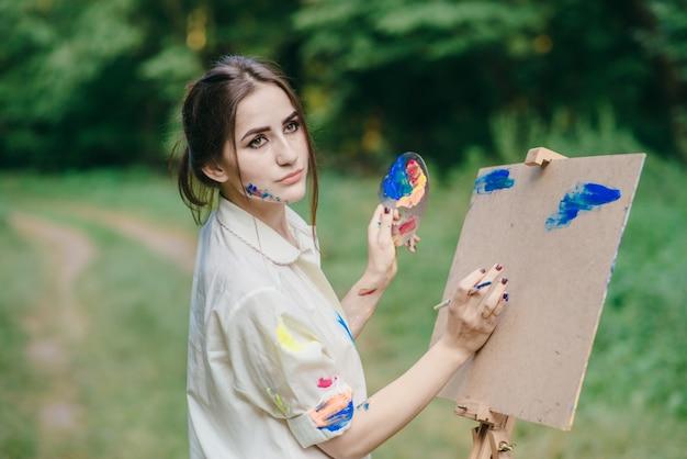 Femme au visage pensif tout en peignant un tableau