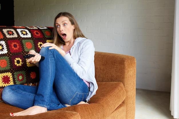 Femme au visage surpris regardant la télé