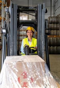 Femme au volant de la machine de chargement d'entrepôt