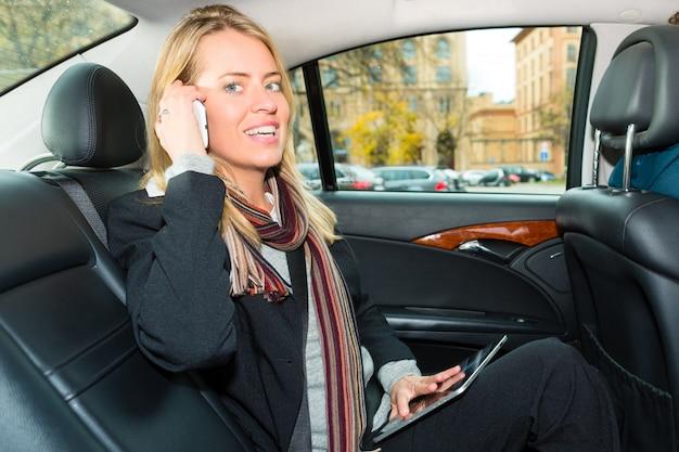 Femme au volant d'un taxi, elle est au téléphone