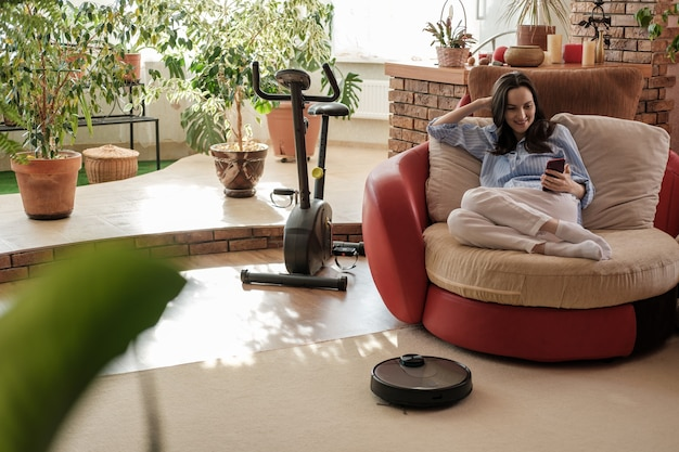 Femme authentique en chemise bleue avec smartphone dans les mains à la maison, aspirateur robot sur tapis, vie chaleureuse et confortable