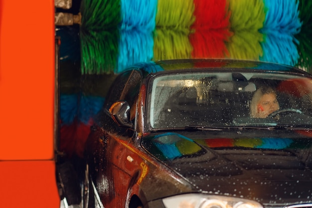 Femme en auto sur lave-auto automatique avec brosse colorée