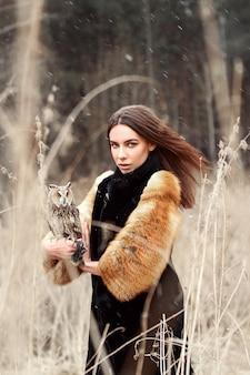 Femme en automne en manteau de fourrure avec hibou en main première neige. belle fille brune aux cheveux longs dans la nature, tenant un hibou. filles au look romantique et délicat